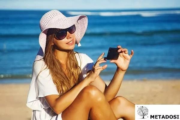 Une jeune femme sur la plage avec un téléphone portable, smartphone