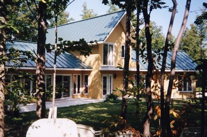 This cheerful yellow home is topped with a lovely dark blue steel sheet roof from Metal Roof Outlet, Ontario.