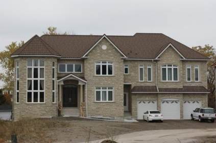 This is the same house, finished! The brown steel continental tile by Metal Roof Outlet is the perfect finish for this taupe field-stone style brick and subtly arched doors and windows.