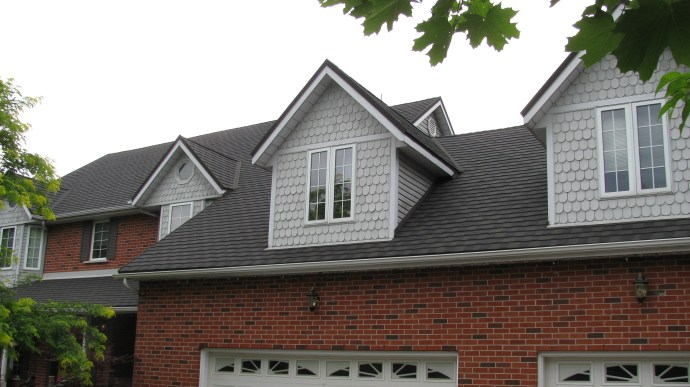 The cool grey scalloped siding of this house is offset by Steel Granite Ridge Shingle in the colour Onyx, installed by Metal Roof Outlet in Ontario.