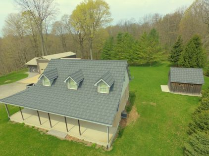 This family home outside of Port Stanley, Ontario features a Metal Shake roof in Weathered Wood, with a little shed to match.