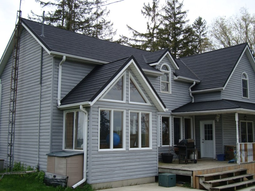 A Granite Ridge metal shingle roof in the colour Charcoal installed on a light blue house