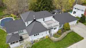Aerial view of a grey metal roof on a white cottage with trees and pool in the background. Cottage located in Port Stanley, Ontario with Tilcor CF Shingle metal roof by metalroofoutlet.com