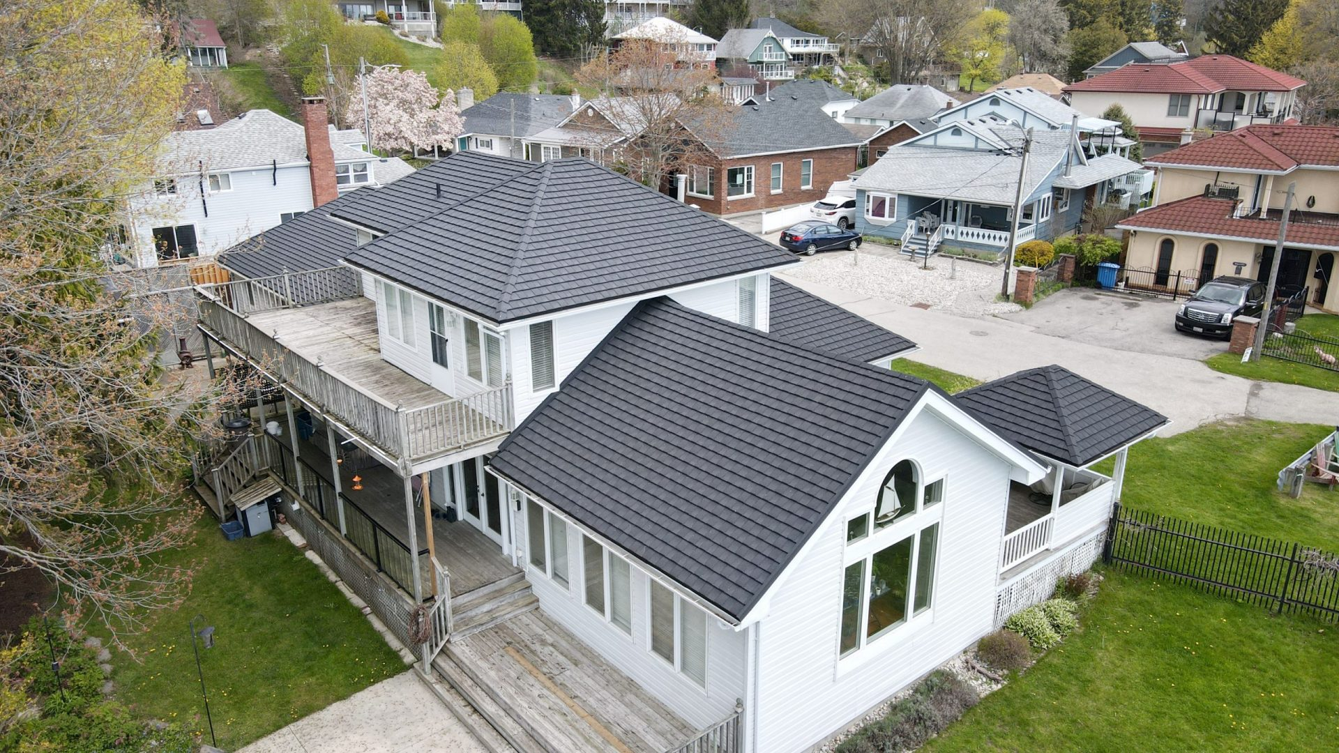 Aerial view of a grey metal roof on a white cottage with trees and cottages in the background. Cottage located in Port Stanley, Ontario with Tilcor CF Shingle metal roof by metalroofoutlet.com