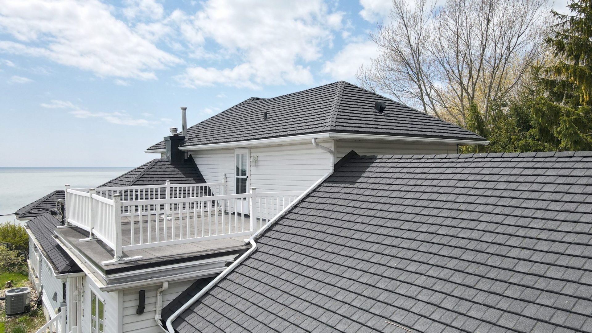 Close up of grey metal shingles from metal roof outlet on a white home with cloudy sky, lake and trees behind