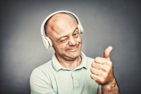 man listening to music on headphones, shows ok,