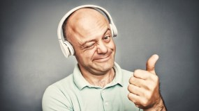 man listening to music on headphones, shows ok,