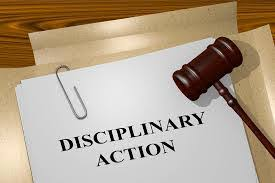 a picture of papers labelled disciplinary action to depict what is a disciplinary hearing