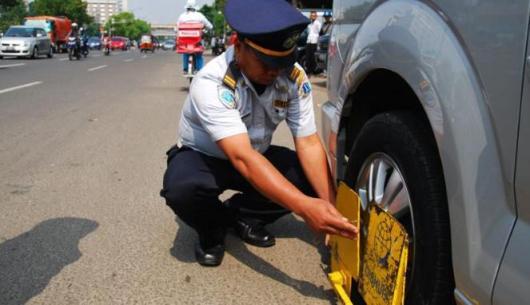 Petugas Dinas Perhubungan (Dishub) lakukan gembok ban bagi kendaraan yang parkir di sembarang tempat.