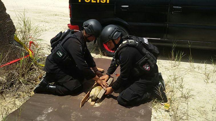 Dua personil Detasemen C Pelopor Satbrimob Polda Kaltim saat mengamankan mortir temuan warga seberat 15 kilogram.