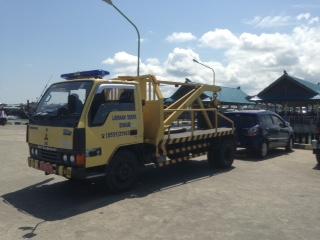 Petugas Dinas Perhubungan kala menderek salah satu mobil yang parkir di dermaga Pelabuhan Tengkayu I cukup lama.