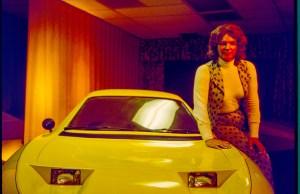 Elizabeth Carmichael sitting on yellow car