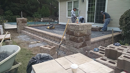 raised paver patio with pillars in