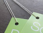 Lime green folded tags strung with 4-ply silver metallic lamé.