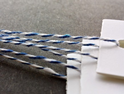 White folded tags strung with blue bakery twine.