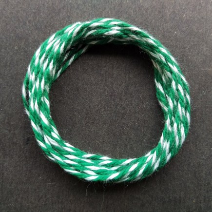 Coil of heavyweight variegated green-white cotton string.