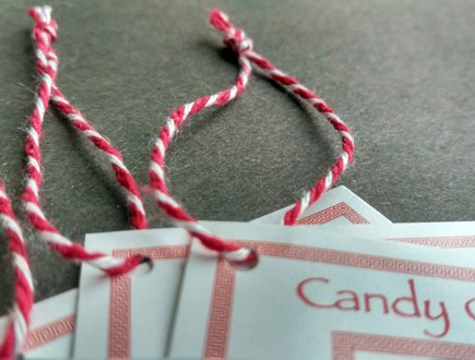 Tags strung with heavyweight variegated red-white cotton string.