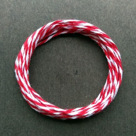 Coil of middle-weight variegated red-white cotton string.