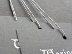 Grey tags with white copy in serif font strung with lightweight 1200 gray Pearlray.