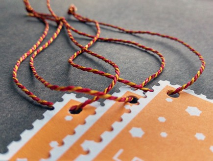 Tags with die-cut edge strung with custom red/yellow 2400 Pearlray.