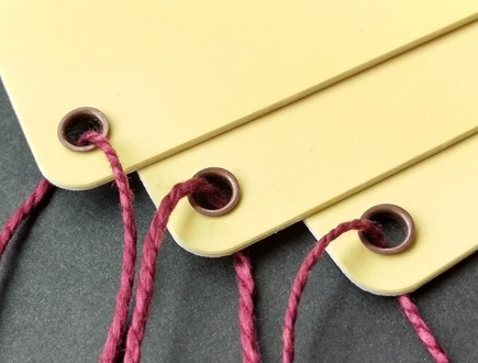 Round-cornered tags of butter yellow double-thick cover stock reinforced with our antique brass eyelets and strung with our wine-tone heavyweight cotton.