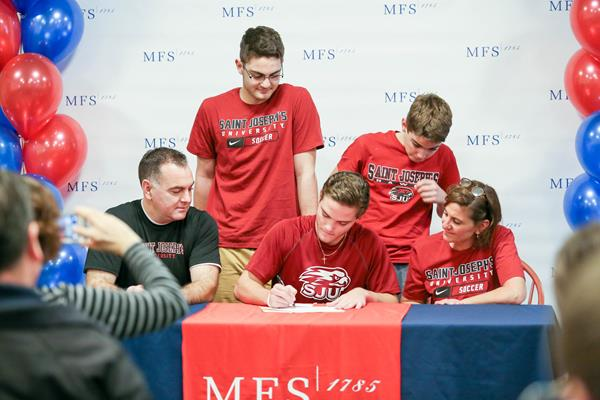 Surrounded by his family, Mullock signs his letter of intent to play at Saint Joseph's University. (Photo courtesy of MFS E-News.)