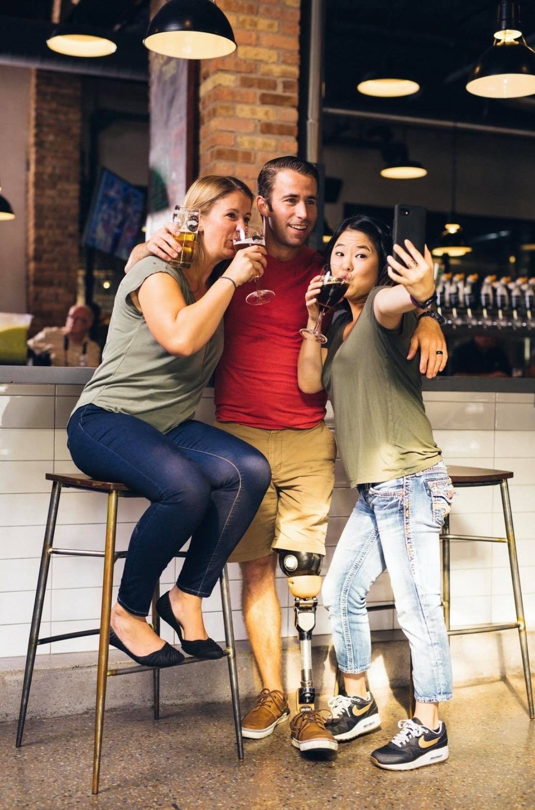 Image appears to be of three people in a bar taking a group selfie. There is a man standing in the middle holding his drink, arms around the shoulders loosely of the two woman and he has a prosthetic leg. The woman on the left leans in posing with her drink up and the woman on the right leans into him pretending to drink and taking the photo with a phone.