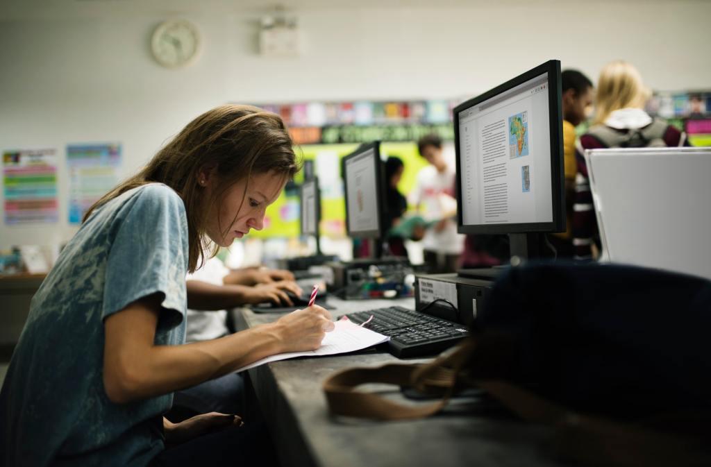 Caucasian woman writing at computer room