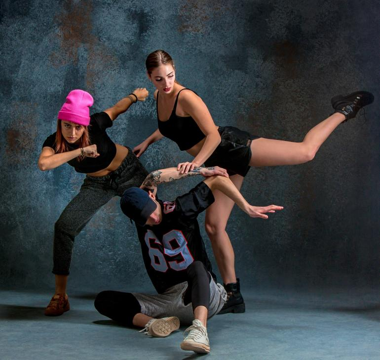 The two young girsl and boy dancing hip hop in the studio