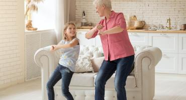 Cheerful older lady with her granddaughter dancing at home