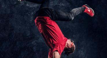 Hip-hop style dancer performs breakdance acrobatic elements.