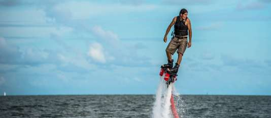 a man flyboarding at sea, miamicurated