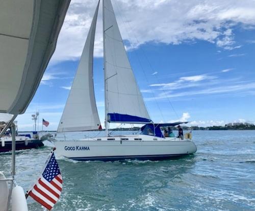 a white sailboat at sea, miamicurated