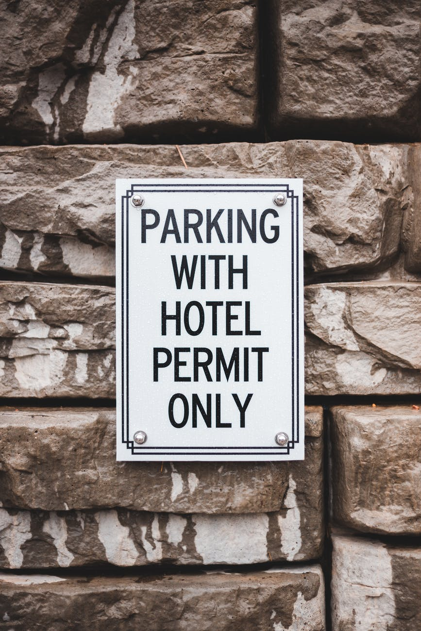 signboard with inscription about parking on stone wall