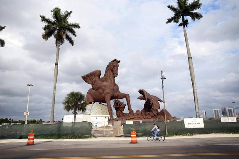 A bicyclist pedals past the $30 million bronze Pegasus statue at the Village of Gulfstream Park that is set to be completed in the coming months.