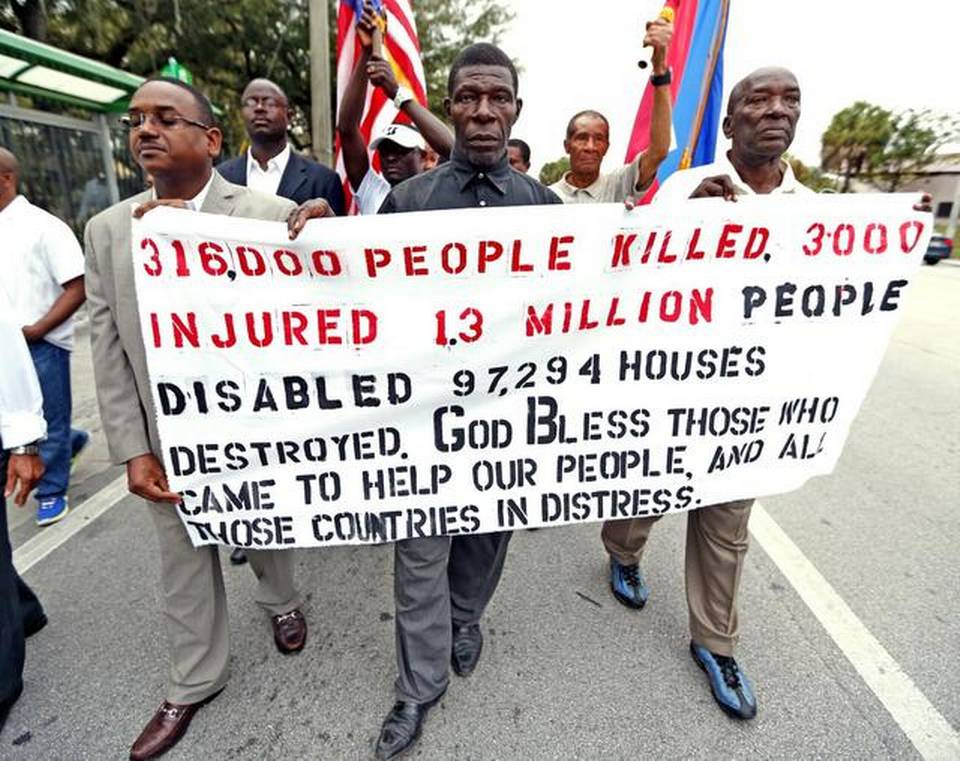 Anis Blemur, Pasteur Germain and Cheker Bacho carry a banner marking the 5th anniversary of the 2010 earthquake that struck Haiti on January 12.