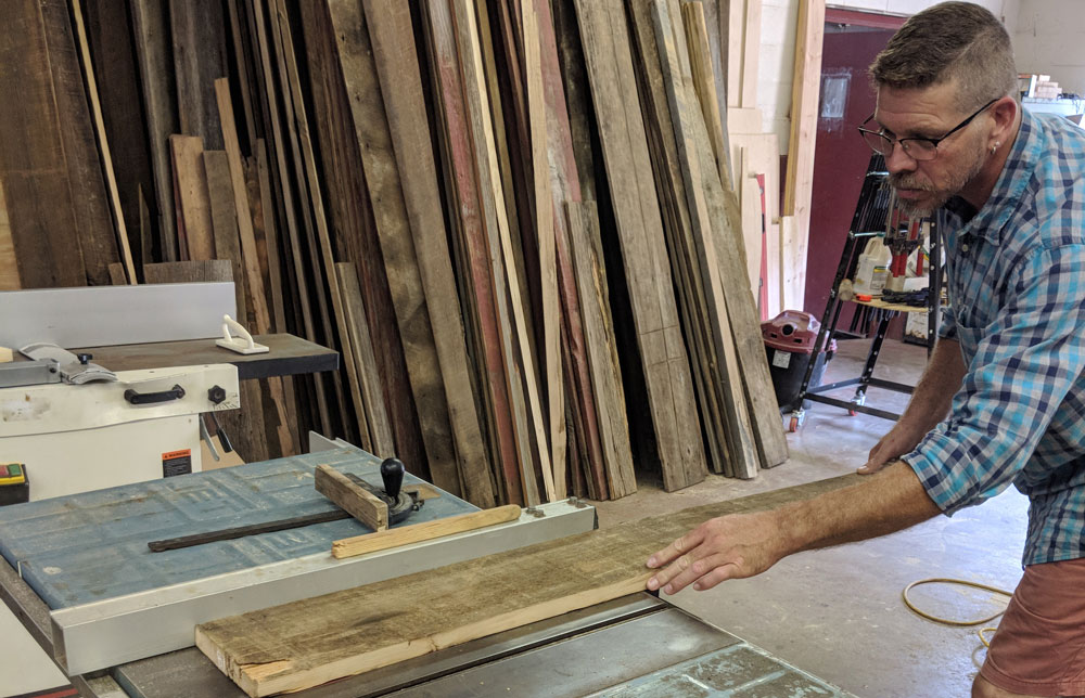 Michael Colemire saws reclaimed lumber for a custom table.