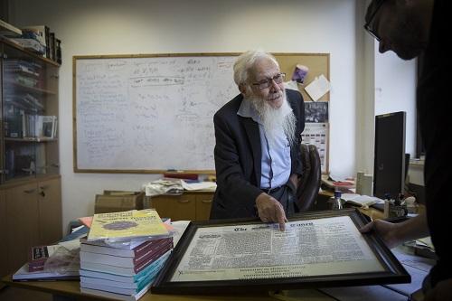 Professor Robert Aumann, shows a framed article from the London Times from 1917 in which the Balfour Declaration on Palestine for the Jews was published, at his office at the Givat Ram campus of the Hebrew University in Jerusalem, August 6, 2014. Aumann recieved the 2005 Nobel Prize in Economics. Photo by Hadas Parush/Flash90 *** Local Caption *** øåáøè éùøàì àåîï ôøñ ðåáì ëìëìä îúîèé÷àé úåøú äîùç÷éí ôøåôñåø øöéåðìéæéä