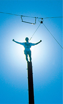 Man standing on top of a telephone pole