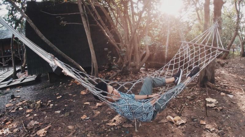 Man in blue shirt lying on hammock