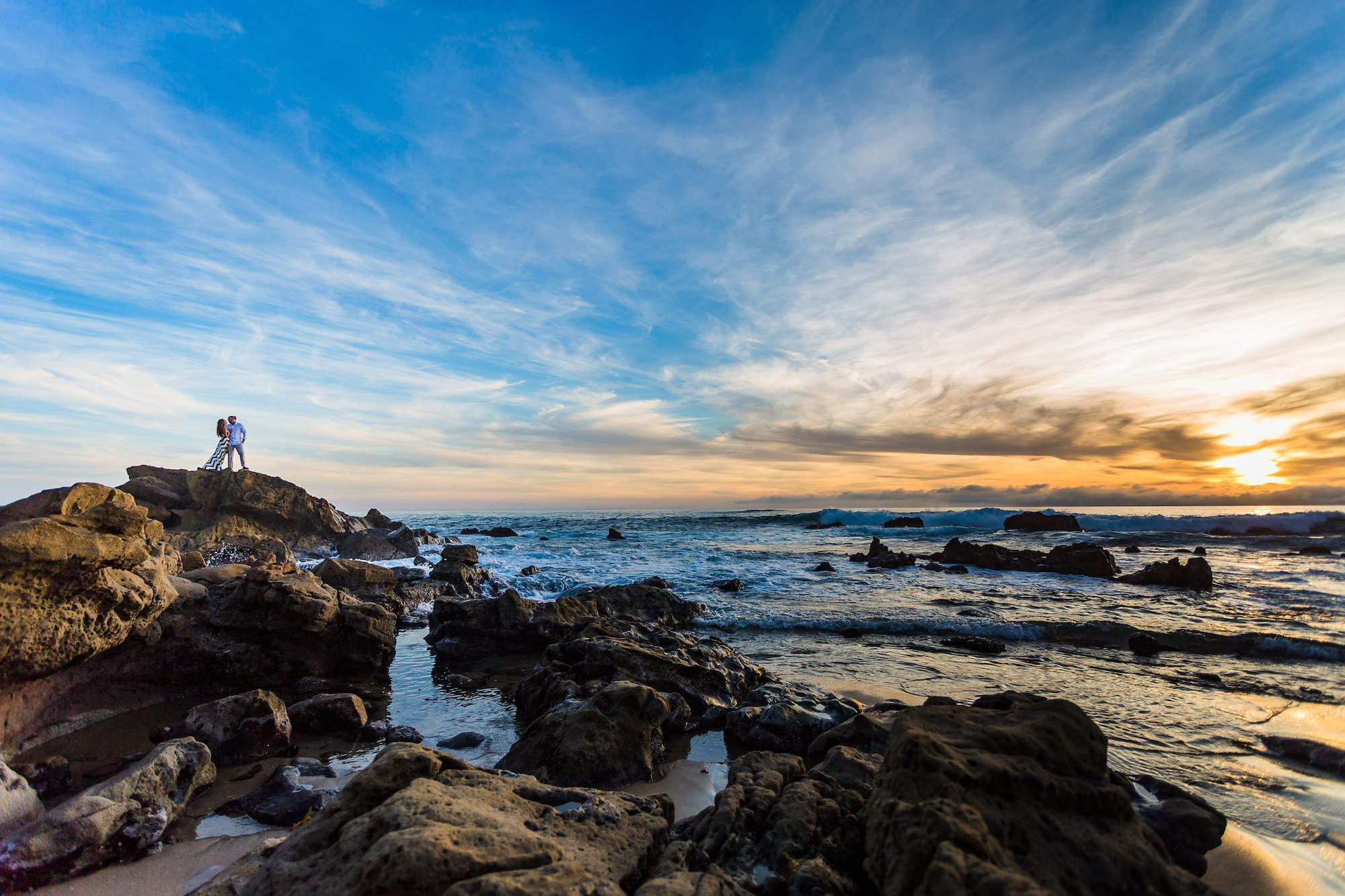 couple kissing on rock in laguna beach