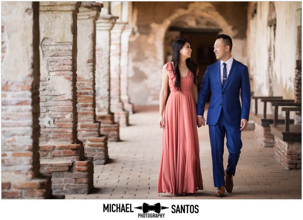 couple walking down the hall during their mission san juan capistrano engagement session