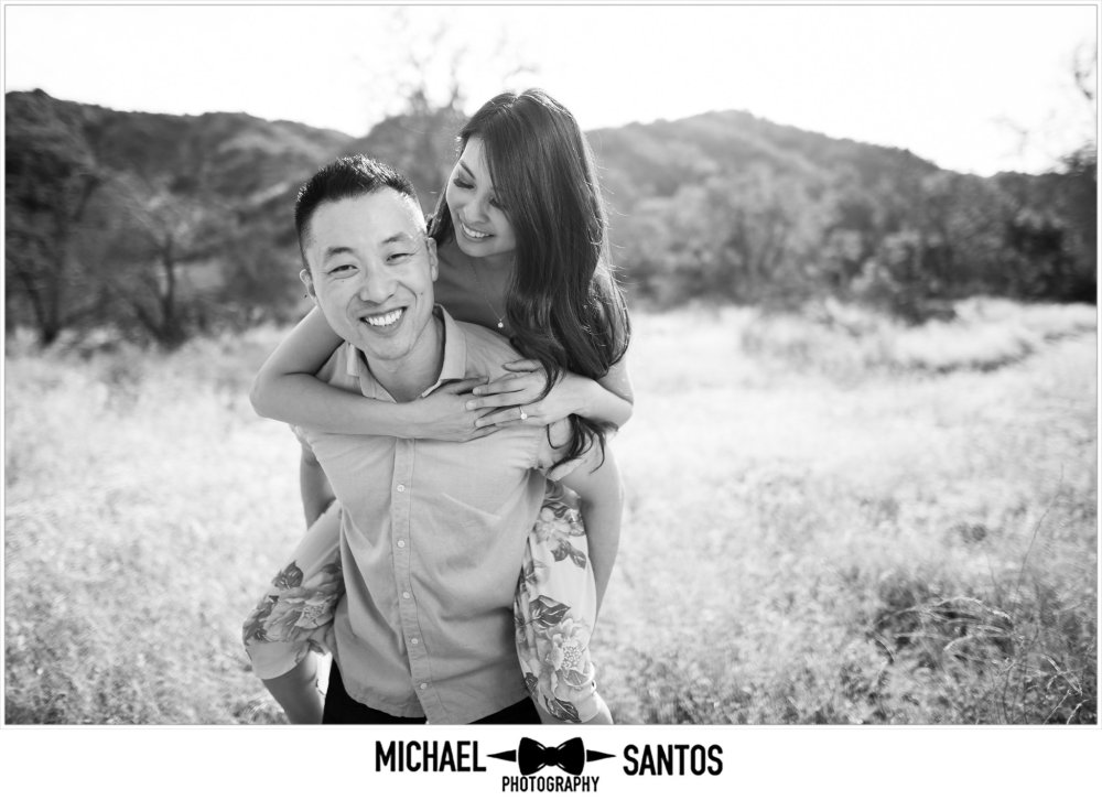 close up of a man giving his fiance a piggyback ride at their caspers wilderness park engagement photography session