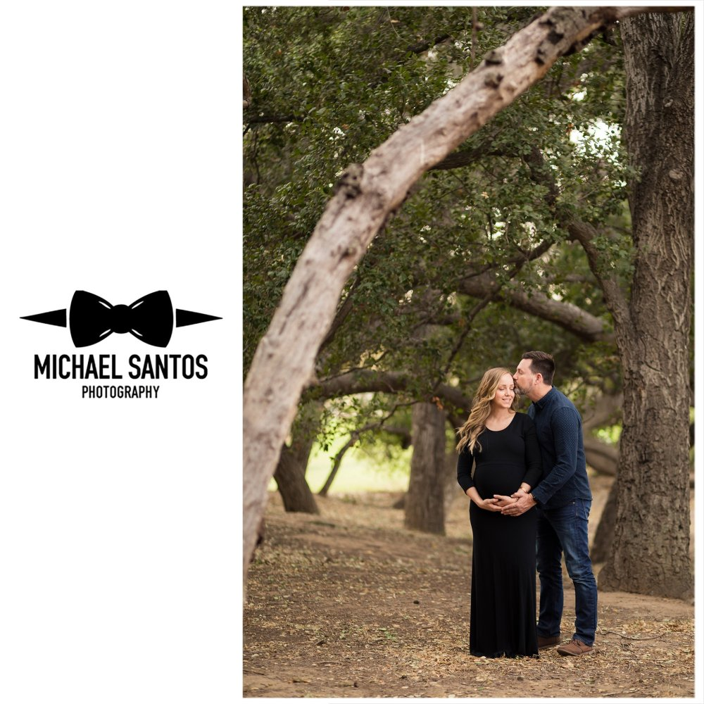 husband kissing pregnant wife on the cheek in the trees at irvine regional park