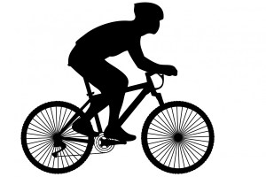 Black silhouette of cyclist wearing helmet to prevent bicycle accident injuries.