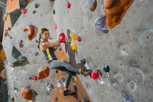 Woman climbing rock wall signed a not responsible for accidents waiver.