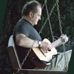 Michel Lelong jouant de la guitare