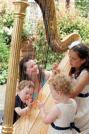 Children trying the harp at a wedding