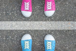 48063000 - blue shoes and pink shoes standing on asphalt concrete floor and white line between them