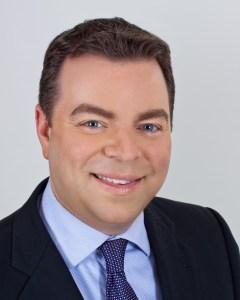 A conservative, formal studio portrait of a business executive.